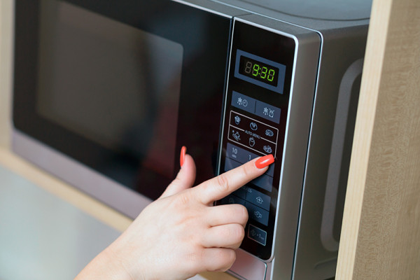 Female hand operating a microwave